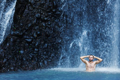 Man having a shower in waterfall Stock Images