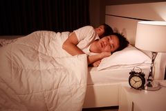 Man having sleepless on bed and having migraine,stress, insomnia Stock Photos