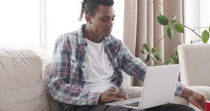 Man having snack and using laptop at home. African american man having breakfast and using laptop at home stock footage