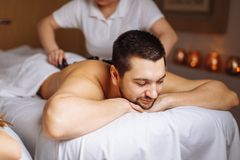 Man having stone massage in spa salon. Healthy lifestyle concept royalty free stock photography