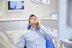 Man having toothache and sitting on dental chair Stock Photo