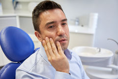 Man having toothache and sitting on dental chair Royalty Free Stock Photos