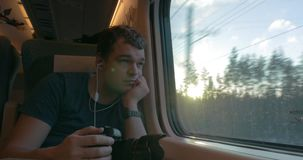 Man traveler shooting video through train window. Man having a train journey. He listening to music and looking out the window after taking a video of outside stock video footage