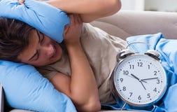 Man having trouble waking up with alarm clock stock photo