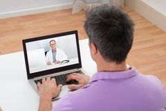 Man having video chat with doctor Stock Photos