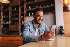 Man having video chat on smart phone at cafe. Happy young man sitting at coffee shot with earphones making video call to friend. Caucasian male having video chat Royalty Free Stock Image