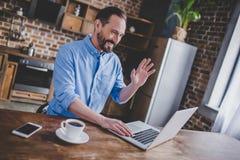 Man having video chat using laptop. Smiling man having video chat with somebody using laptop at the kitchen Stock Photo