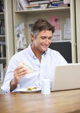 Man Having Working Lunch In Home Office Royalty Free Stock Photography
