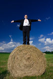 Man on hay bale. Man in a business suit standing on a hay bale Royalty Free Stock Photo