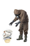 Man in Hazard Suit looking at dirty laundry. A man wearing an NBC Suite (Nuclear - Biological - Chemical stock photo