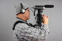 Man with HD SLR camera and audio equipment Royalty Free Stock Images