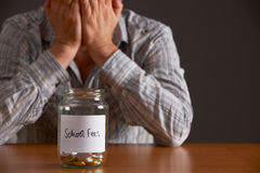 Man With Head In Hands Looking At Jar Labelled School Fees Stock Photos