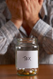 Man With Head In Hands Looking At Jar Labelled Tax Royalty Free Stock Photography
