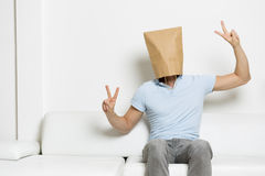 Man with head hidden in paper bag showing victory sign. Anonymous man with head covered by a brown paper bag sitting on sofa and showing victory sign, empty Stock Images