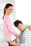 Man with head on his pregnant woman's belly. At home Royalty Free Stock Photos