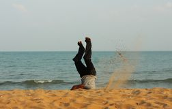 Man head over heels on the beach in India. Auroville Stock Image