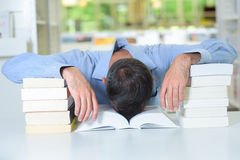 Man with head slumped in book Stock Photos