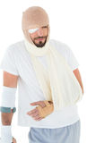 Man with head tied up in bandage and broken hand Stock Photo