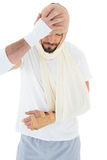 Man with head tied up in bandage and broken hand Royalty Free Stock Photo