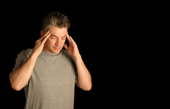 Man with headache. On black isolated background Stock Photos