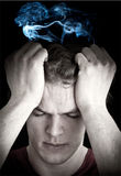Man with headache. Mans face  with  eyes closed holding his head  suffering from a headache, migraine or depressio . Cigarette smoke swirls over his head Royalty Free Stock Image
