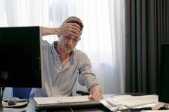 Man with a headache in front of the computer royalty free stock photography