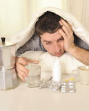 Man with headache and hangover in bed with tablets Stock Photos