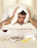 Man with headache and hangover in bed with tablets Royalty Free Stock Photo