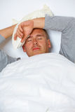 Man with headache in his bed Stock Photography