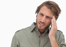 Man with headache looking away and wincing Stock Image