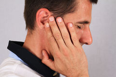 Man with a headache. Man with ear pain, Earache. Pain relief concept Royalty Free Stock Photo