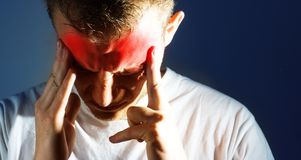 Man with a headache, migraine, suffering from pain Stock Images