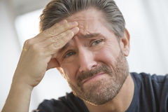 Man With Headache Rubbing Forehead Stock Images