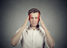 Man with headache thinking very intensely concentrating Royalty Free Stock Image