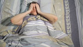 Man with headache waking up in bed at home. Hangover, sleeping and people concept - man with headache waking up in bed at home stock video