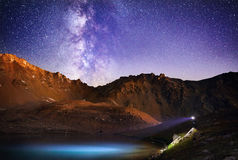 Man with headlight in the mountains at night sky Royalty Free Stock Photos