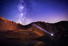 Man with headlight in the mountains at night sky Royalty Free Stock Photo