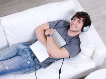 Man in headphone with laptop in an embrace Royalty Free Stock Image