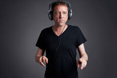 Man with a headphone. A middle age listening some music on the headphone and dancingr Stock Image