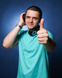 Man with headphones. Listening music at blue background Royalty Free Stock Photo