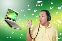 Man with headphones. Oriental Chinese man with headphones plugging in to laptop in green theme Stock Photo