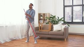 Man in headphones with broom cleaning at home