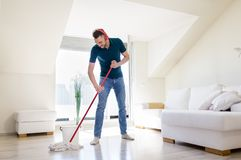 Man in headphones cleaning floor by mop at home Royalty Free Stock Image