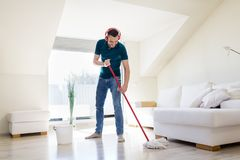 Man in headphones cleaning floor by mop at home Stock Image