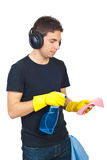 Man with headphones cleaning house. Young man with headphones cleaning house and spraying liquid on duster stock photography