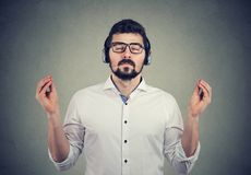 Man in headphones with closed eyes listening to music and meditating. Portrait of a handsome man in headphones with closed eyes listening to music and meditating stock photography