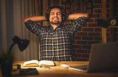 Man in headphones at computer home in evening in dark Royalty Free Stock Photo