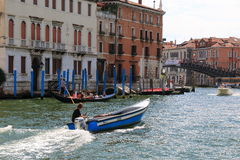 Man in headphones drives the blue motorboat with wooden chest. Venice, Italy - August 21, 2015: Man in headphones listens to music and drives the blue motorboat royalty free stock photography