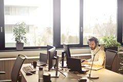 Man With Headphones Facing Computer Monitor Stock Photography
