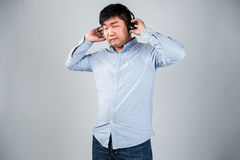 Man in headphones holding mobile phone and smiling Stock Photography